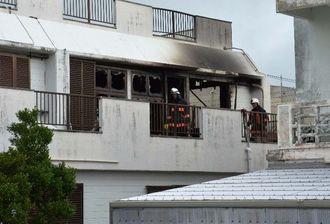 焼け跡から男性1人の遺体が見つかった火災現場を調べる消防隊員ら=2日、八重瀬町宜次
