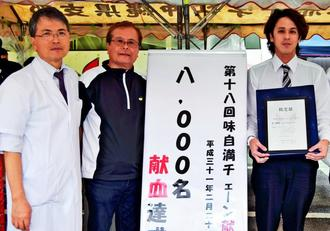 味自満チェーンが協力を呼び掛ける献血で8千人目となった長濱翼さん(右)=21日、沖縄市胡屋・味自満本店