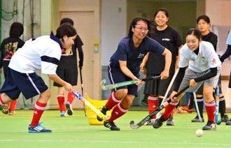 練習に励む首里高女子ホッケー部=浦添運動公園の多目的屋内運動場