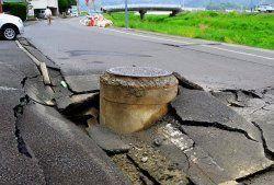 陥没した道路から飛び出たマンホール=4月18日午前10時ごろ、熊本県益城町(新垣卓也撮影)