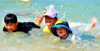 バシャバシャと水しぶきを上げ、歓声を上げながら初泳ぎを楽しむ子どもたち=7日、豊見城市・豊崎海浜公園美らSUNビーチ