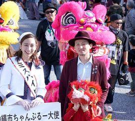 沖縄国際カーニバルのパレードに参加した、ちゃんぷる~沖縄市大使のISSAさん(右)=2018年11月24日、沖縄市・コザゲート通り