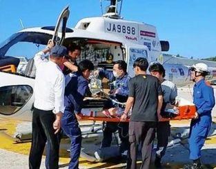 本部港からヘリで搬送される男性=8日(MESHサポート提供)