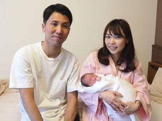 元日に生まれた長男を抱っこした城間未菜さん(右)と宏一さん=1日、那覇市内