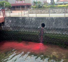 アメリカンビレッジを通り海へと続く水路に流れ込む赤い液体=5日、北谷町美浜(読者提供)