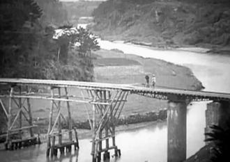 比謝川と嘉手納町の製糖工場につながる橋(シネマ沖縄提供)