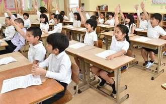 担任の先生の言葉に手を挙げて答える児童=8日午前、豊見城市・上田小学校