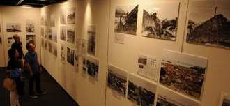 21日からの写真展「よみがえる古里~1935年の沖縄」に向け、当時の撮影フィルムのパネルやカラー化版、新聞記事などを展示した会場=20日、那覇市久茂地のタイムスビル