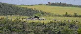ヘリの残骸に近づき、写真を撮るなどして情報収集する日本側の関係者ら=13日午前11時41分、東村高江