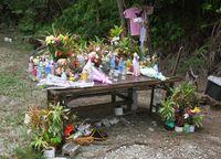 現場献花台 多くの花/恩納村安富祖 被害者悼む