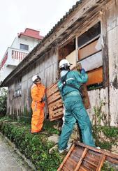 台風25号の強風で飛ばされた雨戸を補強する消防隊員=4日午後4時ごろ、宜野湾市大山(落合綾子撮影)