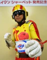 乾燥梅果肉入りのブルーシールアイス「スッパイマンシャーベット」をアピールするスッパイマン=1日、浦添市・フォーモストブルーシール本社