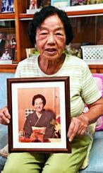 対馬丸沈没時、いかだにしがみついて命を助けてくれた母・キヨさんの遺影を手に当時を振り返る高里シズ子さん=10日、金武町の自宅
