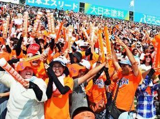 初回先制に盛り上がる興南高校の応援団=11日、甲子園球場