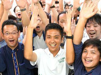 トップ当選を確実にし、支持者と万歳で喜ぶ奥間亮さん(前列中央)=10日午前0時42分、那覇市高良(喜屋武綾菜撮影)