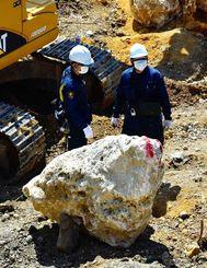 実況見分で積み石を調べる捜査員=午前10時53分ごろ、北中城村安谷屋
