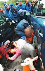橋を封鎖する車両の間に入って抗議する市民らを排除しようとする機動隊ら=22日、東村高江・高江橋