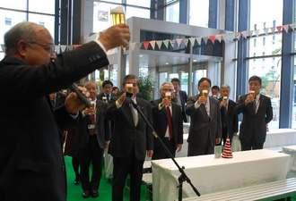 乾杯で麦職人キッチンを開幕した新垣昌光副社長=15日午後、那覇市久茂地のタイムスビル