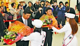 沖縄入りし、歓迎の花束を受け取る広島の緒方孝市監督(左)と梵英心選手=那覇空港