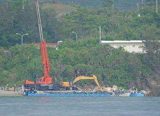 青色の浮遊物をつなげ、再設置が進む桟橋=11日午前8時半ごろ、名護市大浦湾沖