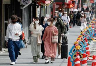 大阪市中央区を歩くマスク姿の人たち=23日午後2時18分