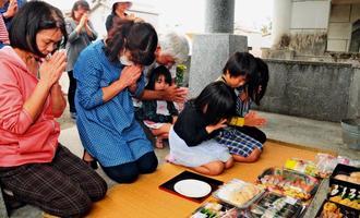 十六日祭で墓前に手を合わせ、一年の無事や健康を祈る親族=3日。宮古島市平良・袖山墓地公園