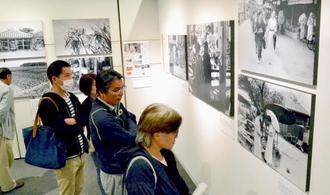 1935年に撮影された写真を眺める来場者ら=31日、横浜市・日本新聞博物館