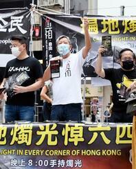 繁華街コーズウェイベイで、市民に向け演説する民主派団体の幹部ら=31日、香港(共同)