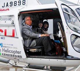 NPO法人メッシュ・サポートの多目的運用第1号となる伊江島での巡回診療に向かう名護療育園の泉川良範施設長(手前)ら=7日午前、名護市宇茂佐・MESHヘリポート