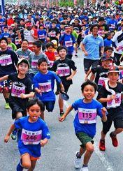 勢いよく走りだすなんぶトリムマラソン・ファミリー種目の子どもたち=20日、糸満市西崎総合運動公園前