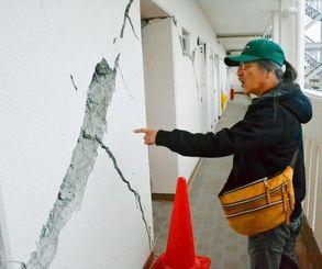 マンションのひび割れを差しながら「恐ろしい地震だった」と語る宮里さん=21日、熊本市