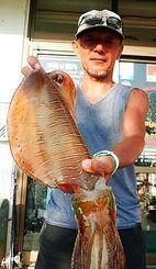糸満釣りイカダで1.59キロのシルイチャーを釣った小松岩夫さん=4月29日