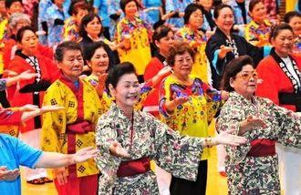 振り付けに合わせて楽しく踊る参加者=28日午前、沖縄市体育館