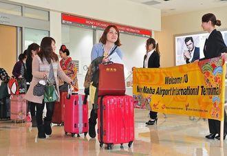 台北からの便で到着し、横断幕で歓迎される観光客=17日午前、那覇空港新国際線ターミナル