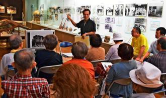 来場者に向けて講話する石川・宮森630の伊波洋正事務局長(奥中央)=8日、うるま市・石川歴史民俗資料館