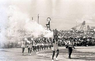 聖火到着式の会場、奥武山陸上競技場を1周する聖火リレー=1964年9月7日、那覇市