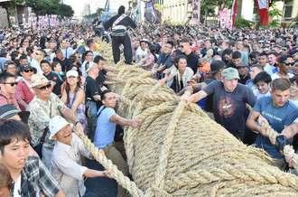「ハーイヤ」の掛け声とともに力いっぱい綱を引く人々=9日午後4時40分ごろ、那覇市・久茂地交差点(金城健太撮影)