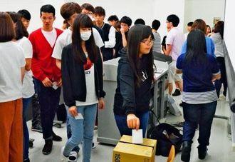 模擬投票で1票を投じる学生ら=3日、那覇市・沖縄大学
