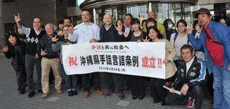 沖縄県手話言語条例が成立し喜ぶろう者や関係者たち=28日、県議会