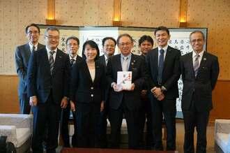 玉城デニー知事(前列中央)に1億円の寄付を報告したはごろもフーズの後藤佐恵子社長(同左から2人目)=31日、県庁