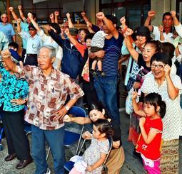 応援する候補者の必勝を期し、ガンバロー三唱で気勢を上げる支持者=8日午後、那覇市内