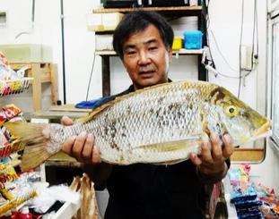 伊是名島で67センチ、3・8キロのタマンを釣った玉城利彦さん=17日