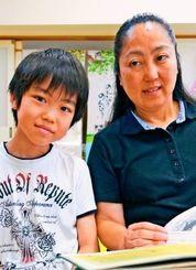 毎年、平和の礎で真栄平家の慰霊を続ける比嘉ゆかさん(右)と長男琉朗君=沖縄市内の自宅
