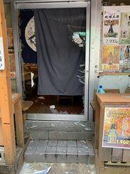 爆発直後の飲食店。出入り口のドアのガラスが割れている=23日、那覇市松尾(読者提供)