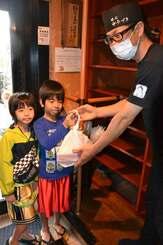 ゆうづきのスタッフ(右端)から弁当を受け取る子どもたち=13日、浦添市内間・ゆうづき本店