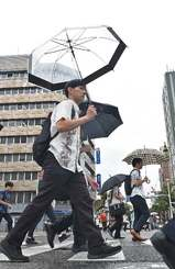 小雨が降る中、足早に出勤する市民=16日午前8時20分ごろ、那覇市久茂地