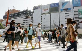 暑い中、マスクを着け歩く人たち。看板の温度計は34度を表示していた=6日午後、東京・新宿