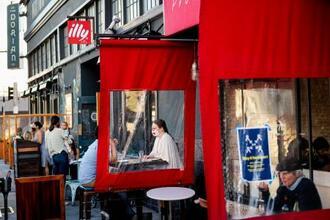 間仕切りのあるレストランで食事をする人たち=21日、サンフランシスコ(AP=共同)