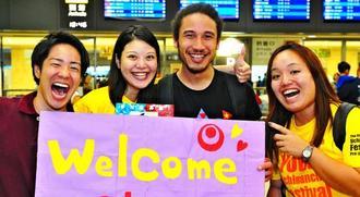 世界若者ウチナーンチュ大会グランドフィナーレでDJを務めるジェフ・タナカさん(右から2人目)と出迎えた実行委のメンバー=16日、那覇空港