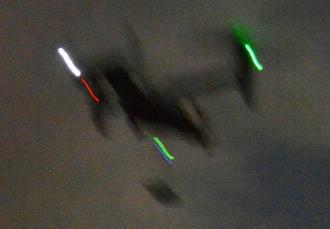 物資をつり下げながら低空飛行で村道上空を横切るオスプレイ=1日午後9時すぎ、宜野座村城原区